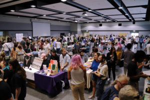 In a large room, people of varying ages, races and gender identities gather around tables, lined up in rows, to look at zines and other DIY arts, crafts and objects.